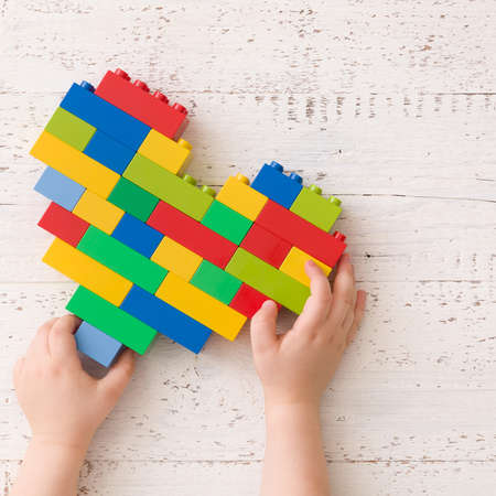 Top view on child's hands with heart made of colorful plastic bricks on white wooden table background.
