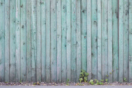 Part of an old rural fence of green wooden boards on the street. Aged wooden plank fence of flat boards backgrounds. Copy space. Stock Photo
