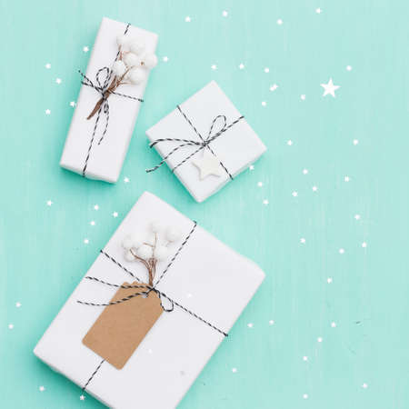 Closeup of beautiful Christmas gifts box wrapped in white paper, Christmas decorations on turquoise wooden background with sparkling stars. New Year, holidays and celebration concept