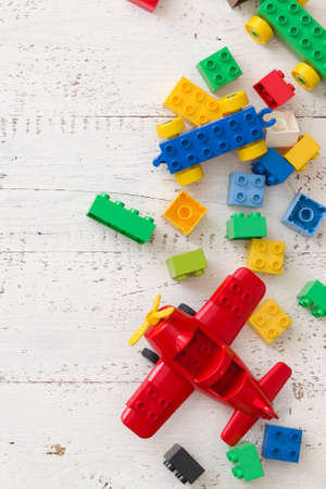 Top view on toy plastic bricks and plane on white wooden table