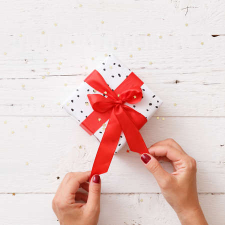 Closeup of young womans hands holding nicely wrapped Christmas or birthday gift box with red satin ribbon on old white wooden background.