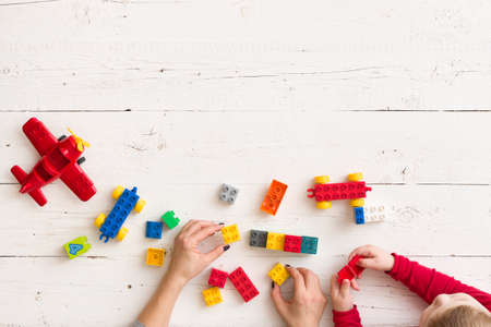 Top view on young womans and childs hands playing with colorful plastic bricks, toys and building from them. Learning by playing.