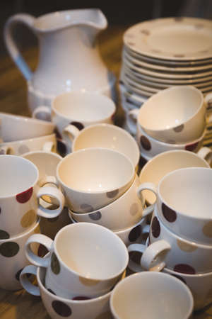 White cups with dark polka dots, a stack of plates and a stylish jug on a wooden table. Preparing for the holiday. Ceramics for the home, dishes, plates, cups.