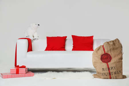 The concept of preparation for the celebration of Christmas and New Years party. There are wrapped presents and bag of Santas with gifts to celebrate Christmas on white sofa on white wall background Stock Photo