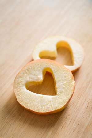 Closeup of two pieces of an apple with heart-shaped holes inside them. Healthy food, vegetarian snack. Stock Photo