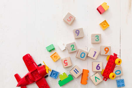 Top view on multi-colored plastic bricks, wooden cubes with numbers 2019 on vintage white wooden background. Education concept