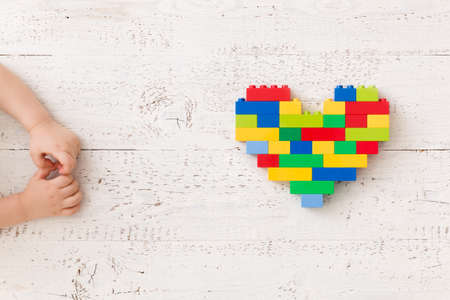 Top view on childs hands playing with colorful bright heart made of plastic bricks on white wooden background or table. Creative idea out of bright constructor bricks. Early learning. Developing toys