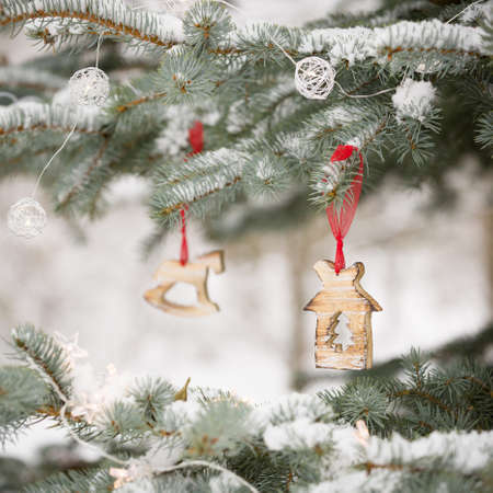 Snowy evergreen tree with nice Christmas decorations on a red ribbon in the winter forest. Winter, Christmas celebration, holidays season concept Stock Photo