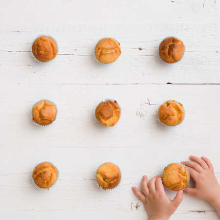 Top view on homemade vanilla muffins places in rows and childs hands on white wooden background. Healthy snack.