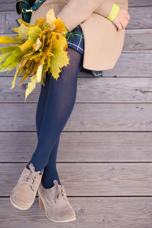 Top view on womans hands holding beautiful bunch of yellow marple leaves. Young woman with bouquet of autumn leaves sitting on wooden bridge in park.autumn, thanksgivining and lifestyle concept