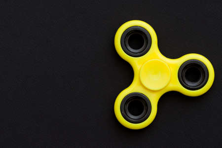 Yellow fidget spinner device on black background.. Top view. Playing with a yellow hand spinner fidget toy Stock Photo