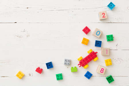 Top view on wooden cubes with numbers and colorful plastic bricks on white wooden table background. School, education and learning concept. Stock Photo