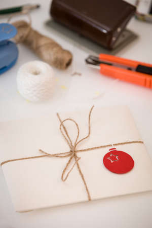 Preparation for Christmas and New Year. Envelopes, cards and handmade decor. Postcard in an envelope with a beautiful decoration and a ribbon. Christmas greetings and concept