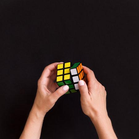 Moscou, Russie, 16 août 2017 : Gros plan du cube coloré dans les mains de la femme. Fille tenant un Rubick's cube coloré et jouant avec sur fond noir.
