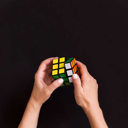 Moscow, Russia, August 16 2017: Closeup of colorful cube in woman's hands. Girl holding colored Rubick's cube and playing with it on black background. Sajtókép