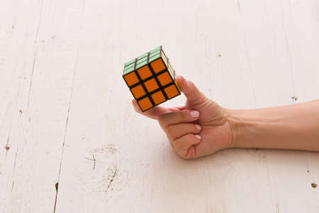 Moscow, Russia, August 24 2017: Rubik's cube in woman's hand, closeup, white wooden background. Girl holding Rubik's cube and playing with it.