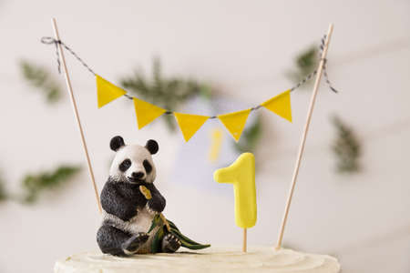 Closeup of beautiful white birthday cake. Celebration delicacy. Healthy carrot cake for 1 year old baby decorated with toy panda and flags banner and fern leaves. Holiday  idea.