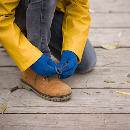 Closeup of cute child tying laces while walking in the city park on a cold autumn day. Stock Photo