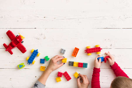 Top view on womans and kid boy hands playing with toys and plastic bricks and building from them on white wooden table background. Learning by playing. Stock Photo