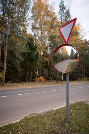 Road sign - give way and outdoor convex protective mirror with a reflection of the urban road look car on a green background.