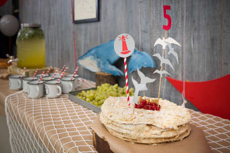 A big white birthday cake with fresh organic red currants, number 5 and nautical theme decor. Festive cake. Homemade berry pie. Cake decor Stock Photo