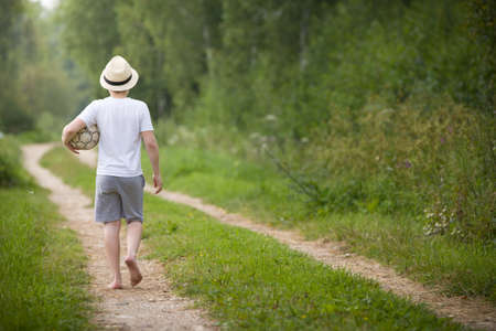 Back view on kid boy in a straw hat walking on a countryside road and playing with football ball. Child outdoors on a sunny summer day. Lifestyle, vacations concept. Stock Photo
