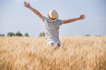 Back view on cute kid boy jumping and having fun while walking on golden wheat field on a summer sunny day. Child running on rye meadow. Outdoors. Countryside.
