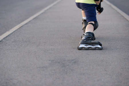 Closeup of black roller skates or rollerblading. Roller skate legs of a child in the park. Boys legs in roller blades. Stock Photo