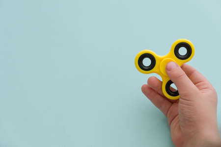Childs hand spinning a fidget spinner device on light blue background. Top view. Playing with a yellow hand spinner fidget toy Stock Photo