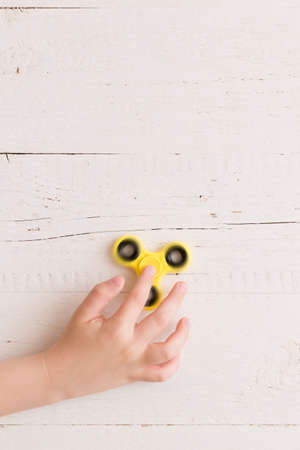 Childs hand spinning a fidget spinner device. Top view. Playing with a yellow hand spinner fidget toy Stock Photo