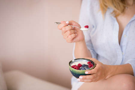 Woman sitting on a sofa and eating organic yogurt with blueberries and raspberries. Girl in blue shirt having healthy breakfast at home.