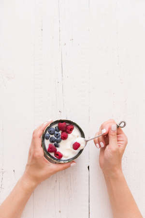 Top view on womans hands holding small bowl with organic yogurt with blueberries and raspberries on white wooden background. Girl having healthy breakfast at home. Healthy eating, snack. Stock Photo