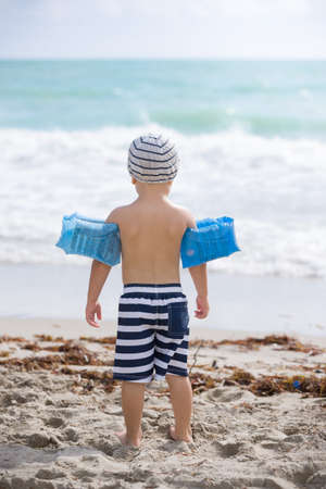 Miami, USA, October 07 2017: Back view on cute toddler boy wearing safety inflatable armbands standing on the beach ready to jump into ocean or sea. Safety first. Vacations. Stock Photo