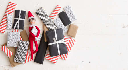 Top view on Advent calendar presents wrapped in colorful paper and small Christmas toy on white wooden background