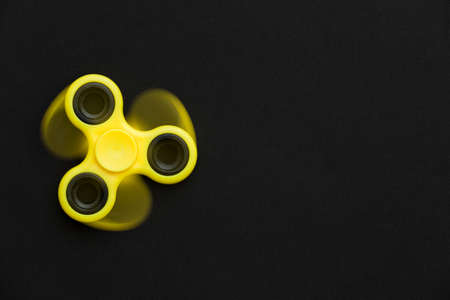 Rotating yellow fidget spinner device on black background. Top view. Playing with a yellow hand spinner fidget toy