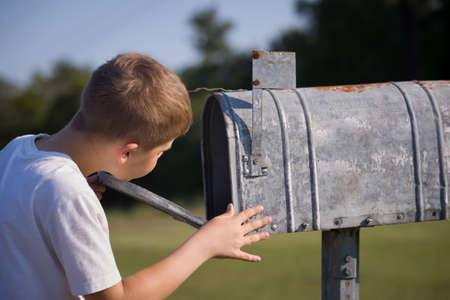 Kid boy opening a post box and checking mail. Kid waiting for a letter, checking correspondence and looking into the metal mailbox.