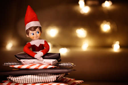 Closeup of elf with gifts on the background of garlands. Christmas and holidays concept Stock fotó