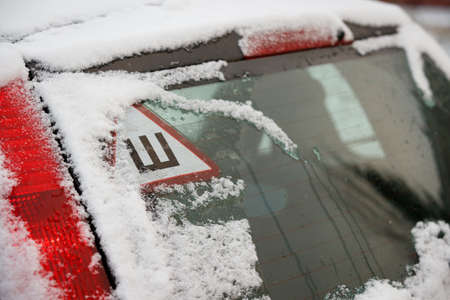 Sign of studded tires on the rear window of the car. Safe movement on snow covered roads Archivio Fotografico