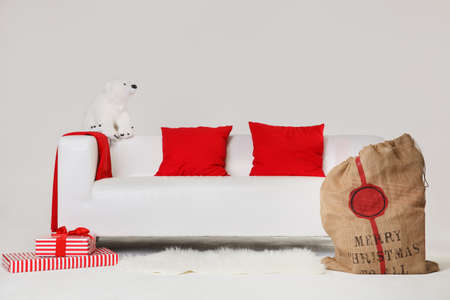 Preparing for the celebration of Christmas and New Year. Wrapped gifts and Santa's bag with gifts to celebrate Christmas on a white sofa against a white wall background. 스톡 콘텐츠 - 113931262