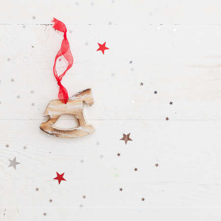 Closeup of wooden horse Christmas decoration on vintage wooden background with shiny stars. New Year, holidays and celebration concept Stock Photo