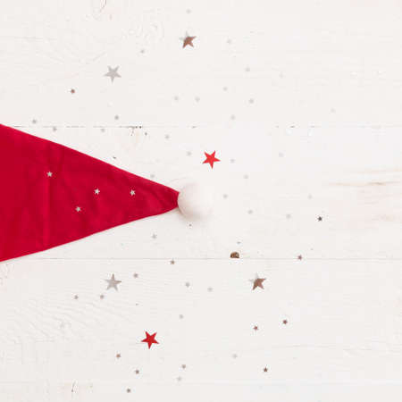 Closeup of Santas red hat on old white wooden background with shinny silver stars. Christmas, winter and holidays season concept. Stock Photo