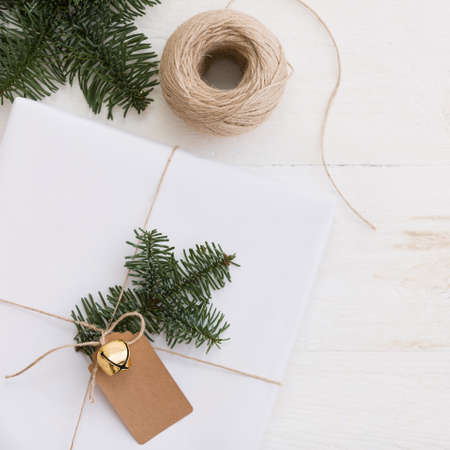 Top view on Christmas gift in white paper decorated with tree branch and tag Stock Photo