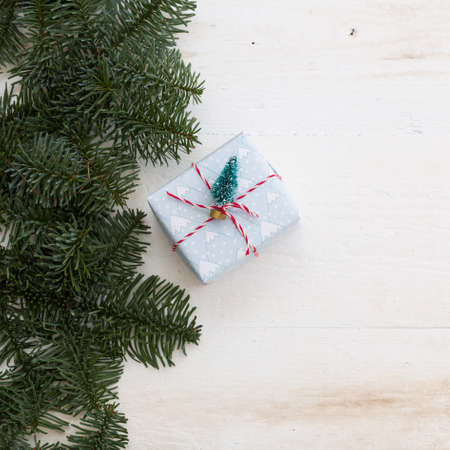 Closeup of Packing Christmas gifts box on white wooden table or background.