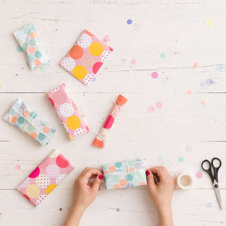 Top view on girls hands with nicely wrapped Christmas or birthday gifts on white wooden table background. Holiday season. Stock Photo