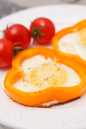 Fried organic eggs inside orange paprika rings. Eggs with tomatoes and paprika. Healthy breakfast or snack. Healthy food.