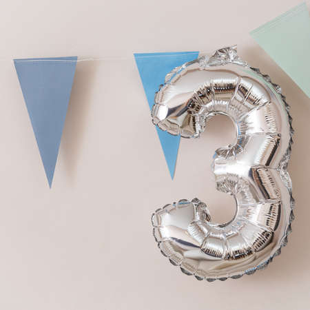 Closeup of number 3 silver colors and blue paper garland flags on white wall background. Celebration concept