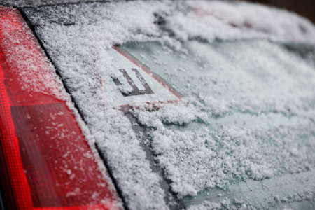 A car sticker with a Russian letter meaning spikes on the rear snow-covered glass of the car warns drivers that the car is equipped with studded wheels. Safe movement on snowy roads