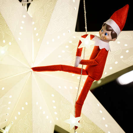 Closeup of funny Christmas elf is hanging on a garland, against the background of a large paper Christmas star. The concept of Winter and Christmas