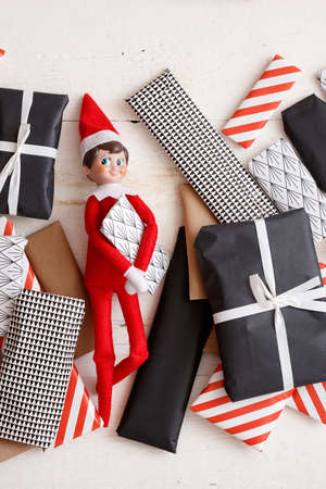 Hugging elf with Christmas gifts on a white wooden background. View from above. Christmas and holiday concept