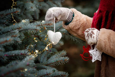 The hands of the girl in mittens are holding a New Year tree decoration. Decorated Christmas fir tree in the background. New Year and Christmas concept